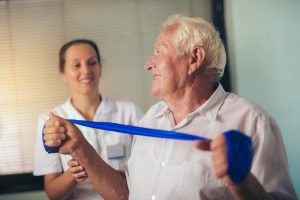 man doing occupational therapy with a home health nurse